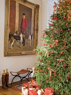 The traditional Christmas tree in the front hall of this New Orleans home is decked in red, complementing the antique painting and Oriental rug of this living room.