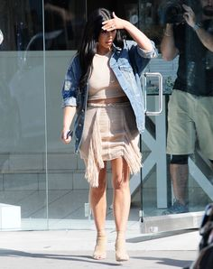 Kardashian hit the streets of L.A. in a crop-top and fringe skirt by Balmain, which she wore under a R13 distressed denim jacket with nude Aquazzura booties.