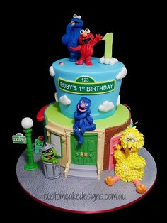 This cake was made for little Ruby who is a big fan of Sesame Street and is turning 1! :) To add a little bit more interest to the cake, it was decided to create a Sesame Street 'street scene' which runs along the base / bottom tier and includes Elmos house, Big Birds house, Hoopers Store and a generic brick building in the street. The cake is made from white choc mud and caters for approx 65 desert / 130 coffee sized portions