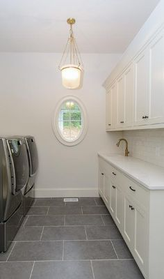 A glass lantern hangs over gray staggered floor tiles in front of an oval window flanked by a gray front loading washer and dryer and white shaker cabinets fitted with oil rubbed bronze hardware and a curved countertop holding a sink with a brass gooseneck faucet in front of a white subway tile backsplash lining white upper cabinets.