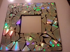 Break old CDs to create a mosaic frame. I love the way it reflects light!