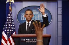 A reporter's hand goes up as U.S. President Barack Obama concludes remarks from the Briefing Room of the White House in Washington August 20, 2012. REUTERS/Kevin Lamarque