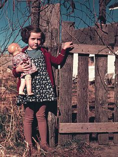 Rare color photos: Kids in the 1940s  1941 or 1942   Girl with doll standing by fence