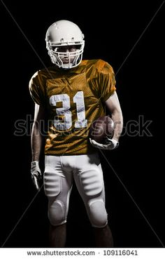 Football Player with number on the orange uniform and a ball in the hand. Studio shot.