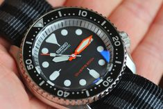 Seiko SKX007, Modded by Yobokies with a double-domed sapphire crystal, orange plongeur hands, and a silver chapter ring, on a bond NATO strap. The only thing I would maybe add is a Planet Ocean style bezel insert. Maybe.