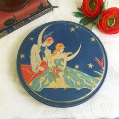 Lovely 1920s Chocolate tin featuring a pretty lady and her suitor in set against the night moon. This box would make a beautiful decorative storage box on your vanity, jewelry box or just display.  Antique Art Deco tin litho Chocolate box, Blue Moon, Queen Anne, Romantic w/ Lovely Lady, girl woman, jewelry box, dresser trinket, round candy canister, courtship  10x1.25  See pics for wear, this antique tin has the usual age wear, scratches, fading and patina, I DO ship Internationally and ...