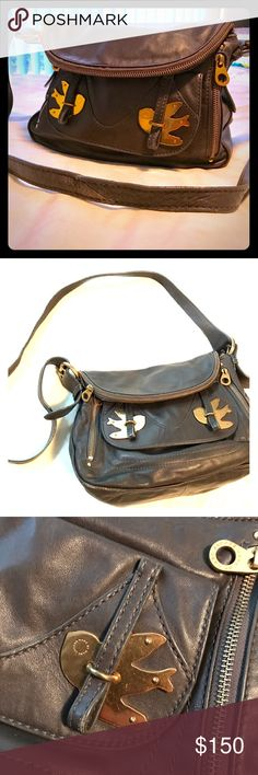 Marc Jacobs Petal to the Metal Natasha Crossbody Darling Brass Birds on the front and a trim buckle strap gently cinches the back slip pocket for a pretty finish. Adjustable shoulder strap. Loads of exterior zip, slip and magnetic-closure pockets. Interior slip pockets and a zip pocket. Goldtone hardware. Warm gray leather. Well loved but shows signs of wear. Marc Jacobs Bags Crossbody Bags