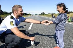 A young refugee girl plays with a police officer on a closed highway during a break. The refugees were trying to march across Denmark to get to Sweden and were escorted by the police that tried to convince the refugees to cancel their march.
