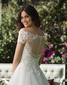 Heavily beaded, embroidered lace bodice and full tulle skirt adorn this off the shoulder basque waist ball gown with short sleeves and an illusion back.