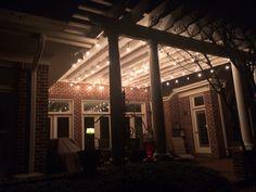Edison bulbs on a backyard patio. Red brick. Pergola. Edison string lights.