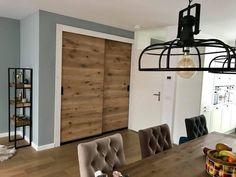 Op maat gemaakte schuifdeuren achterelkaar met zwart stalen frame ingelegd met hout voor trapopgang en trapkast.