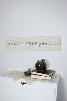 By grace you have been saved. Ephesians 2:8 Shown in white distressed paint and black writing. Size: approximately 8 x 30 Unique hand-painted sign made from reclaimed wood, comes ready to hang with sawtooth hangers on the back. Please keep in mind that because this sign is made from reclaimed barn wood, no two will ever be alike, and it will not look exactly like the photo. Colors can be customized. Base: Black paint, white paint, distressed white paint, dark brown stain Writing: Black…