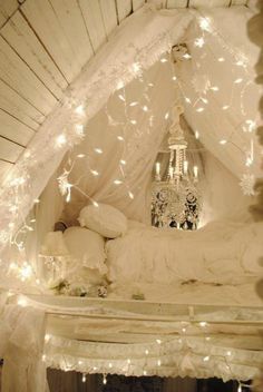 I love this idea for bedroom lofts. The sheer curtains along with white Christmas lights that are strung up take the eye off the small room and make it look fabulous