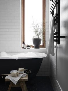 Beautiful bathroom, white tile, black claw foot tub, wood framed window