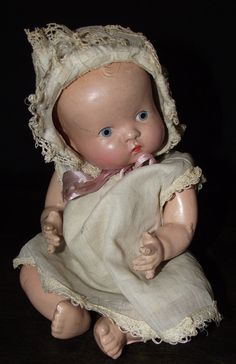 Incredibly adorable tiny, blue-eyed, baby doll! Shes wearing a little dress, panties and bonnet. This doll is unmarked and is in great condition for