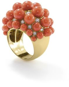 A coral and diamond ring  Of bombé design, set with rows of graduating coral beads to brilliant-cut diamond highlights, ring size M.