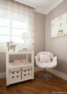Cortina e quadro com detalhes de borboletas rosas, parede cor nude, poltrona de amamentação e cômoda