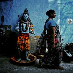 A lady walks past a life size clay idol of a hindu deity (lord shiva) in the…