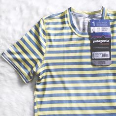 "Patagonia Striped Gray & Yellow Slim Fit Tee Brand new Patagonia striped shirt in XS. Material is made up of 84% Polyester and 6% Spandex. This is the slim fit style called the ""Capilene"" graphic tee. Measurements are 16"" bust and 24.5"" in length. Please ask if you have any questions. Bundle & Save Patagonia Tops Tees - Short Sleeve"