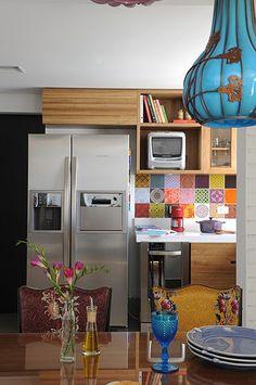 O painel de azulejos coloridos acima da bancada, assim como alguns dos objetos, traz vida ao ambiente. O armário de madeira catuaba confere aconchego