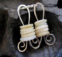 MOP buttons earrings - wire through 2 holes & curled underneath.  This wire's been hammered flat.