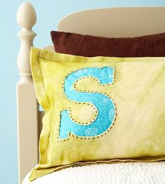 Monogram Pillow made of wool felt, cut out letter, back with complimentary fabric, and hand stitch the two layers together with embroidery floss