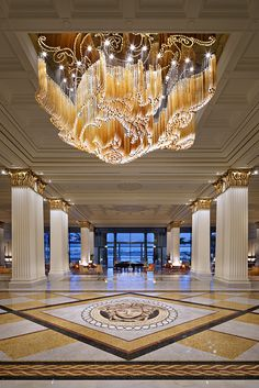 Golden Breeze installation by Lasvit for Palazzo Versace  The layout of the amber-tone and crystal-clear elements of Golden Breeze is based upon a classic Versace floral pattern. It's designed to appear as if moved by a soft breeze, bringing delicacy to a 3000 kg work of hand-blown glass. Placed prominently above the central floor mosaic, the subtle elegance of this lighting sculpture supplements a surprisingly restrained lobby design, welcoming guests to a rich and unforgettable space…
