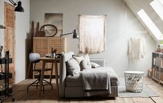A spare room with a sloped ceiling is furnished with neutral coloured furniture, including a a sofa bed and a desk.