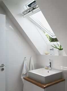 An operable venting VELUX skylight with venetian blinds brightens and refreshes this bathroom.
