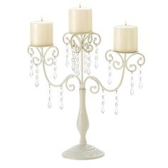 Dripping with glittering crystals, graceful ivory curlicues create a showy support for a trio of candles. Delightfully extravagant with a touch of Old-World ele