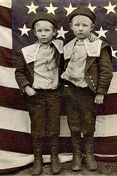 Cute boys in front of American Flag. They have such a sad look in their eyes, can't help but hope they had a good life.