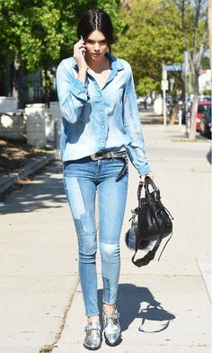 Kendall Jenner wears a denim top, belted jeans, and silver oxfords with a black bucket bag