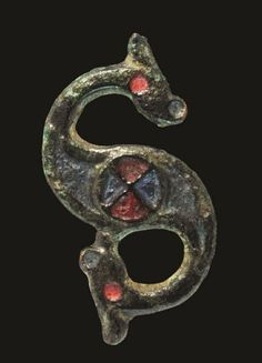 Iron Age Celtic Enamelled Bronze Dragonesque Brooch    1st century BC . A cast bronze dragonesque brooch with red enamel to the eyes, red and blue to the central roundel and flanking panel