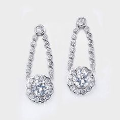 High quality cubic zirconia drop earrings feature a 1.0 carat brilliant round accented with round stones attached to a double strand of small bezel set round stones. An approxiamate 3.18 total carat weight, measure 1 1/8th inches long. These beautiful earrings are set in 14k white gold. Cubic zirconia weights refer to equivalent diamond carat size.