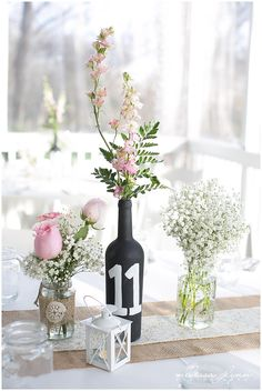 simple table arrangements with table number markers. Brides personal touch to table centerpieces, with larkspur, roses and baby's breath. Flowers  by Bloom and  Leaf Event Florist.  Photo by Melissa Glynn Photography