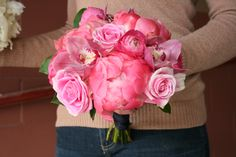 Coral charm peonies, pink ranunculus, pink cymbidium, and pink roses. All pink bridesmaid bouquet.