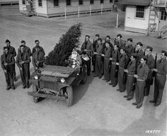 Santa delivering a Christmas tree to the troops in a Jeep Willys MA.
