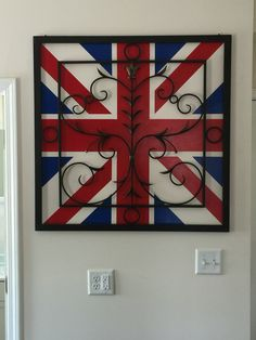 Union Jack painted on the wall with metal wall art hanging on top.