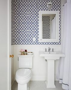Fantastic bathroom features top half of walls clad in navy squiggles wallpaper, Cole & Son Vivienne Westwood Squiggle Wallpaper, and lower walls clad in white beadboard finished with a white chair rail lined with a pedestal sink under an white framed inset medicine cabinet flanked by a toilet to the left and a white shower curtain with navy trim to the right.