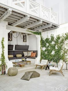 The courtyard holds teak lounge chairs by Henry Hall Designs, a custom-made banquette with cushions in a Perennials fabric, and antique Spanish lanterns found in Belgium.