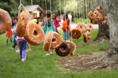 Donut eating game - with no hands, just like an animal.  :)  It might be hard to keep kids away from this for very long...I wonder if they could be pre-strung, but kept in a donut box, then suspended between the trees right before you had the game?