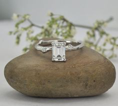 A beautiful, organic twig engagement ring, mounted in a 4 prong basket setting set with an emerald shaped center stone. The aesthetic of the natural twig texture and the classic setting is creating a nature-inspired ring that is unique and elegant. HERE ARE THE DETAILS:  ❀ CENTER STONE: Forever One Moissanite. 100% colorless ❀ STONE SHAPE: Radiant-cut emerald ❀ STONE SIZE: 7 x 5mm =1.20 Carat ❀ RING WIDTH: between 2-3mm  CERTIFICATE: ❀ Forever Brilliant Charles & Colvard Created Mois...