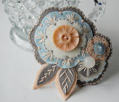 Lovely felt button brooch @Chris Cote Staatz . This is lovely & a Great example of embroidery stitching.