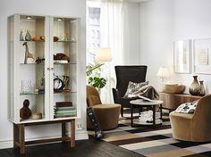 Ett vardagsrum med beige skåp med glasdörr och ben i massivt askträ samt två snurrfåtöljer täckta av mörk beige sammet. Här med en svart fåtölj med hög rygg och ett litet runt soffbord.