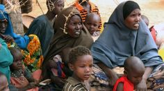 FILE - Somali women and children sit under a tree at a refugee camp in Dolo, Somalia. Relief agencies say 300,000 children under 5 can no longer get vaccinated against major childhood killers like measles or treated for diarrhea.