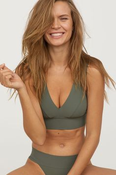 Khaki green. Bikini top with a lined, shaped front section. Wide shoulder straps, wide elastication at lower edge, and wide metal fastening at back.