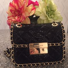 "MICHAEL Michael Kors Carine Med Bag Jewelry for your shoulder! Luxe look with downtown edginess makes for a new classic!  Quilted black patent python embossed leather and yellow gold tone hardware glistens gently and boldly.outer sleeve pocket with snap; inner zip pocket , three card slots and divider sleeve pocket. Chain doubles for shoulder wear 14""approx and can slide singly to 23""for possible cross body wear. Dust bag and care card incl. MICHAEL Michael Kors Bags"