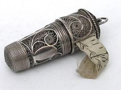 a tall filigree thimble containing a glass scent bottle (original) with a filigree tape measure screwed onto the base. The tape is original but missing the first few inches