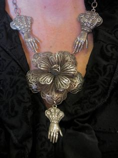 Antique Mexican Sterling Silver Filigree Flower Necklace with Vintage Hand Charms. $480.00, via Etsy.