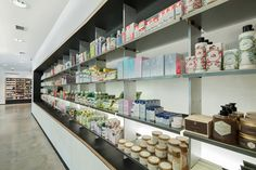 Mills Pharmacy -   Built-in millwork cabinets alternate between various plywood grades: a white panel commonly used for highway signs, a black slip-resistant veneer, and common fir plywood in the market lining both ends to create a wall of candy. Stand-alone displays are fabricated from hot rolled metal frames and laser cut steel shelves. A new, burnished concrete floor unites all of the new public spaces for clients.
